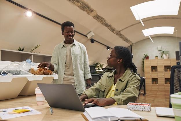 현대 사무실에서 쓰레기 분류 빈에 종이 컵을 넣어 웃는 아프리카 계 미국인 남자의 초상화, 복사 공간
