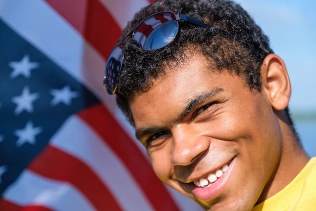 미국 국기 배경에 서 있는 웃는 아프리카계 미국인 남자의 초상화