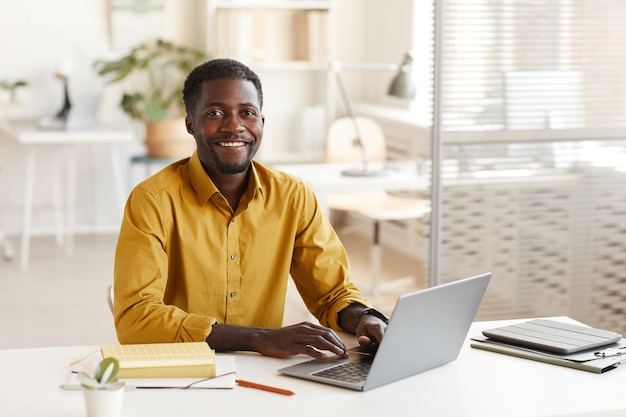 노트북을 사용하고 최소한의 사무실 인테리어에서 작업을 즐기면서 카메라를보고 웃는 아프리카 계 미국인 남자의 초상화, 복사 공간