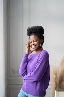 トレンディなジュエリーの大きなイヤリングで笑顔のアフリカ系アメリカ人のミレニアル世代の若い女性の肖像画は、自宅で立ってポーズをとって紫色のセーターを着ています。カメラを見てアフロ髪型の陽気な女の子。