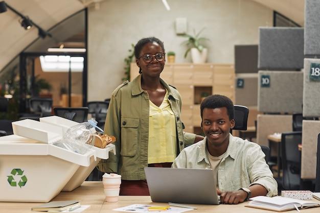 현대 사무실에서 쓰레기 분류 쓰레기통에 의해 포즈를 취하는 동안 웃는 아프리카 계 미국인 사람들의 초상화, 복사 공간