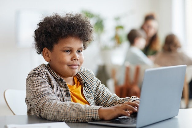 クラス、コピースペースでラップトップを使用して笑顔のアフリカ系アメリカ人の男子生徒の肖像画