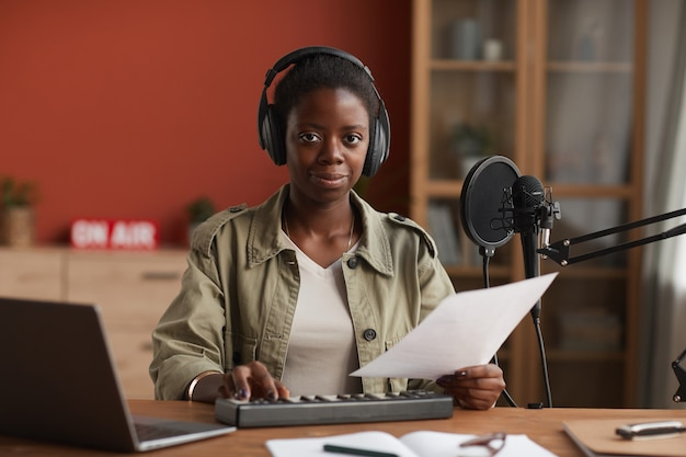 녹음 스튜디오에서 음악을 작곡하는 동안 카메라를보고 헤드폰을 착용 웃는 아프리카 계 미국인 여자의 초상화, 복사 공간