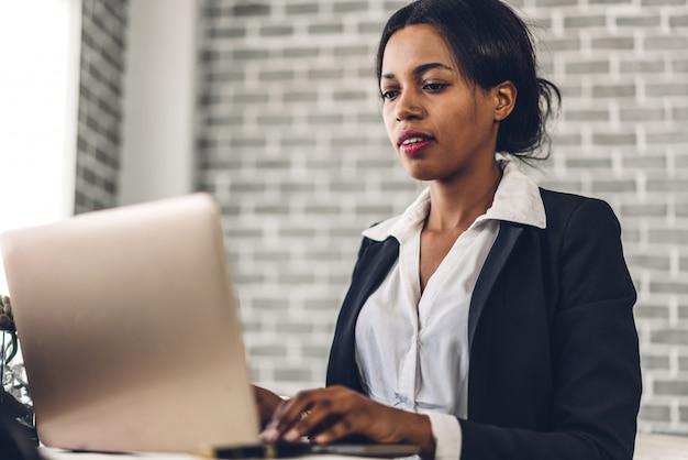 Портрет улыбающейся афро-американской женщины, использующей ноутбук