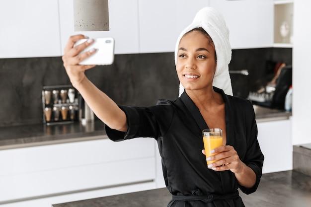 キッチンで携帯電話でselfieを取る、バスローブを着て笑顔のアフリカ系アメリカ人女性の肖像画
