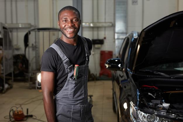 Портрет улыбающегося африканского работника автосервиса на рабочем месте