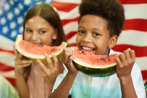 Портрет улыбающегося африканского мальчика, держащего арбуз с американским флагом