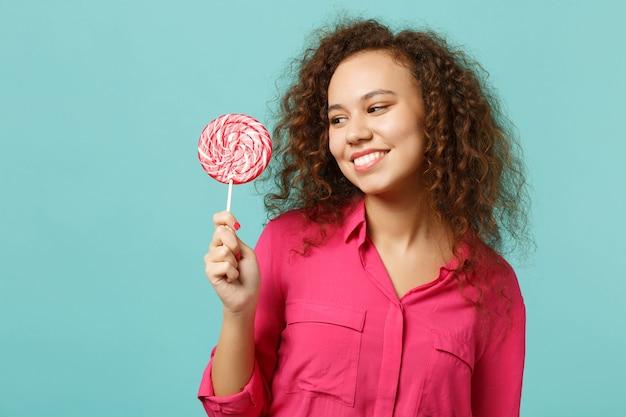 스튜디오의 파란색 청록색 배경에 격리된 분홍색 둥근 롤리팝을 바라보며 캐주얼한 옷을 입은 웃고 있는 아프리카 소녀의 초상화. 사람들은 진심 어린 감정, 라이프 스타일 개념입니다. 복사 공간을 비웃습니다.