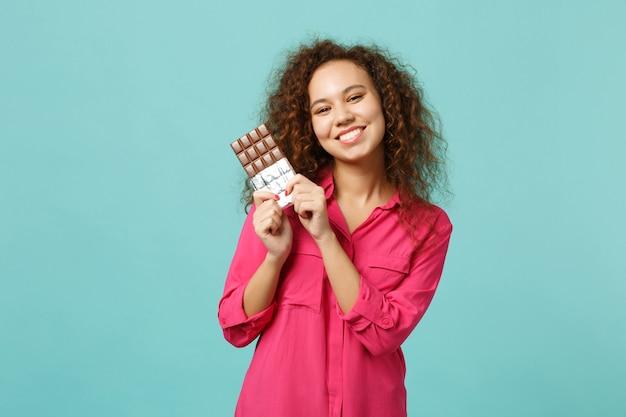 스튜디오의 파란색 청록색 벽 배경에 격리된 초콜릿 바를 손에 들고 캐주얼 옷을 입고 웃고 있는 아프리카 소녀의 초상화. 사람들은 진심 어린 감정, 라이프 스타일 개념입니다. 복사 공간을 비웃습니다.