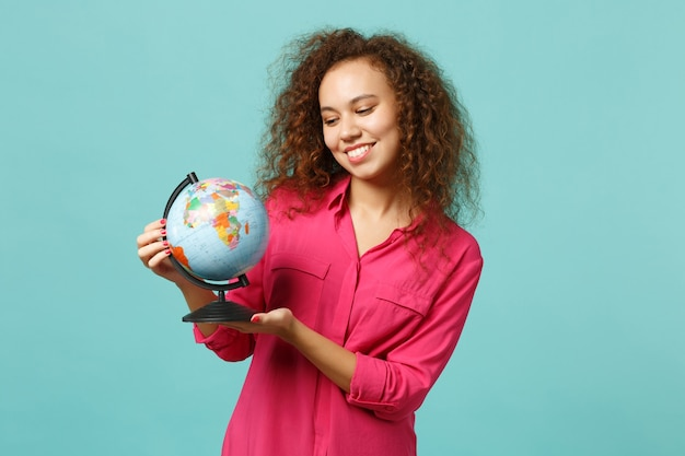 Портрет улыбающейся африканской девушки в повседневной одежде, держащей в руках глобус мира земли, изолированных на синем бирюзовом фоне в студии. люди искренние эмоции, концепция образа жизни. копируйте пространство для копирования.