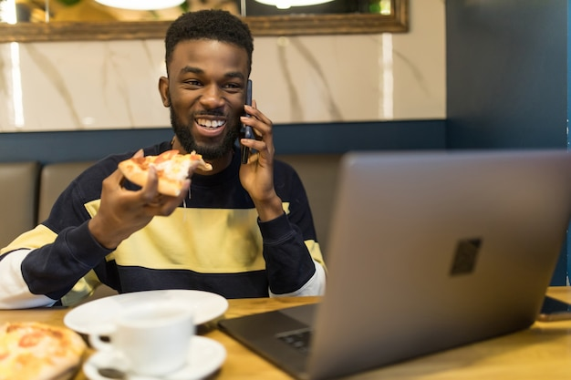 Портрет улыбающегося африканца разговаривает по мобильному телефону, сидя в кафе с помощью ноутбука и обедает
