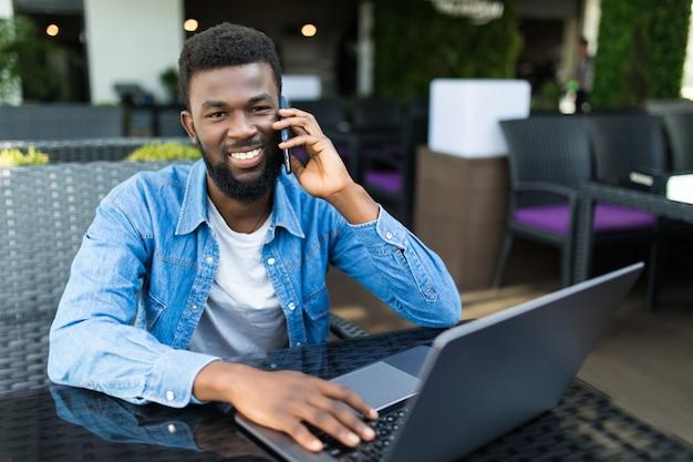 Портрет улыбающегося африканца разговаривает по мобильному телефону, сидя в кафе с ноутбуком