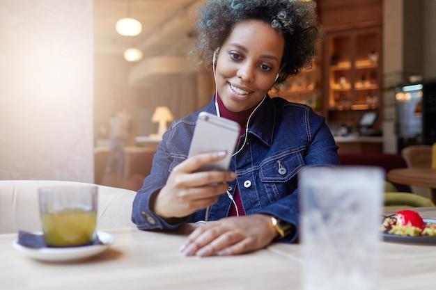 Портрет улыбающейся африканской женщины, сидящей в кафе и слушающей музыку по телефону