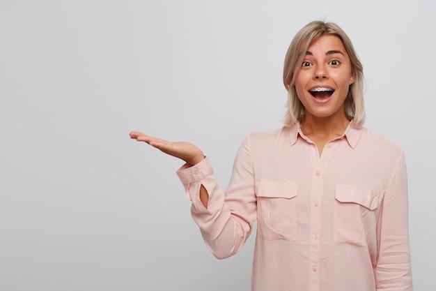 치아 교정기와 입을 열고 놀란 금발의 젊은 여자 미소의 초상화는 분홍색 셔츠를 입고 놀란 모습과 흰 벽 위에 절연 손바닥에 copyspace를 들고