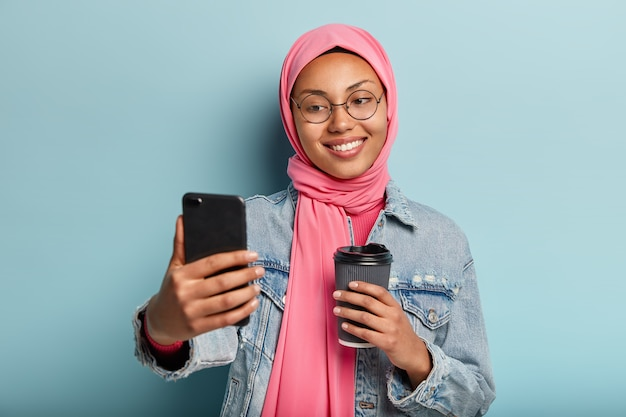 Портрет улыбающейся арабской девушки делает селфи на мобильном телефоне