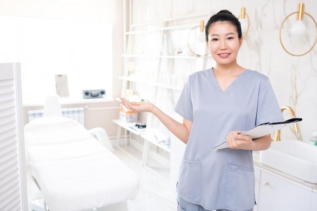 클립 보드와 함께 서서 피부 관리 절차를 수행하도록 초대하는 스크럽에 웃는 아시아 미용사의 초상화