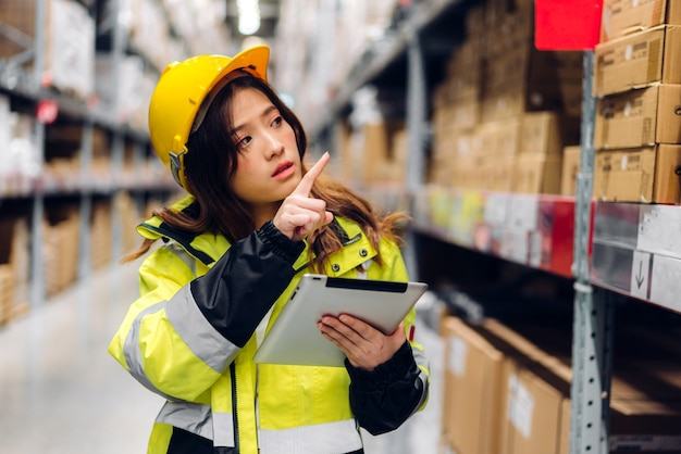 ヘルメットの女性の笑顔のアジア人エンジニアの肖像画は、棚の商品や消耗品をチェックするためのタブレットコンピューターで詳細を注文します