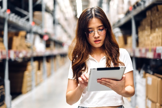 태블릿 컴퓨터에 헬멧 여자 주문 세부 정보에 웃는 아시아 엔지니어의 초상화