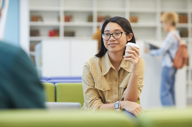 大学図書館で勉強しながらコーヒーを楽しんで笑顔のアジアの女の子の肖像画
