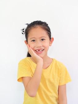 Портрет улыбающейся азиатской маленькой девочки со сломанным зубом и рукой, касающейся его щеки