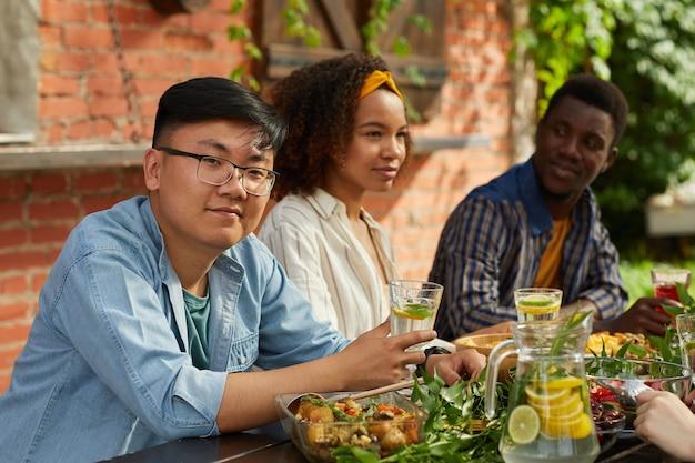 여름 파티 동안 야외 테이블에 앉아 친구와 함께 저녁 식사를 즐기고 웃는 아시아 남자의 초상화
