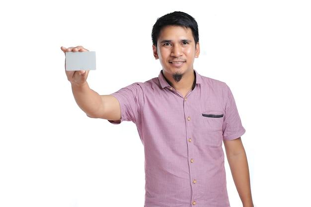 白い背景の上の白い空白の名刺を保持している笑顔のアジア人男性の肖像画
