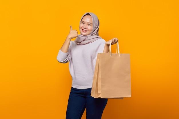 ショッピングバッグを持って、黄色の背景の上に親指を表示して笑顔のアジアの女性の肖像画
