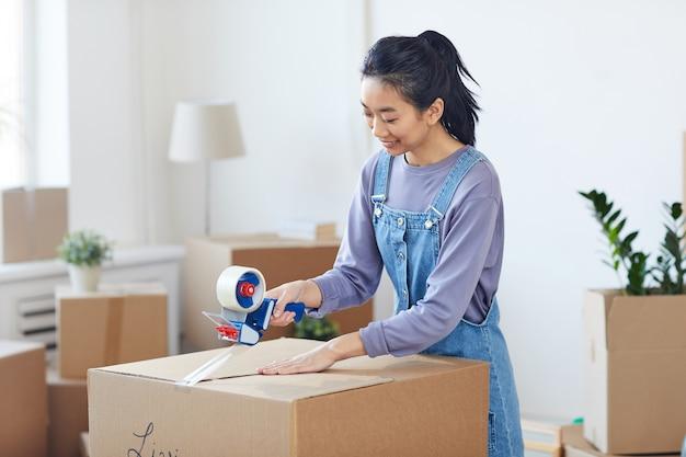 Stが新しい家に移動しながらテープディスペンサーで段ボール箱を梱包する笑顔のアジアの女性の肖像画