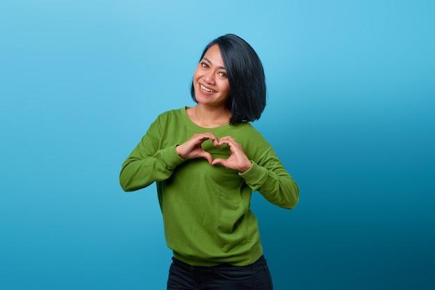 青い背景に両手でハートジェスチャーを示す笑顔のアジアの女性の肖像画