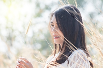 Portrait of smiling asian women with grass flower