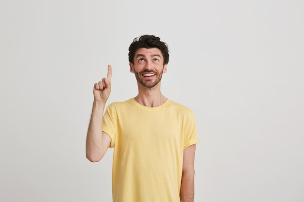 Портрет улыбающегося привлекательного бородатого молодого человека в желтой футболке выглядит счастливым и показывает пальцем вверх, изолированным на белом