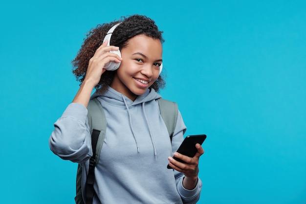 Портрет улыбающейся привлекательной черной девушки с афро-прической, синхронизирующей беспроводные наушники со смартфоном во время прослушивания музыки