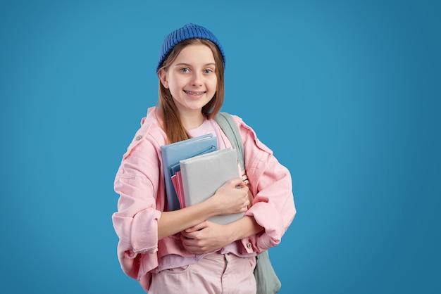Портрет улыбающейся привлекательной девушки с подтяжками, стоящей и держащей кучу учебников
