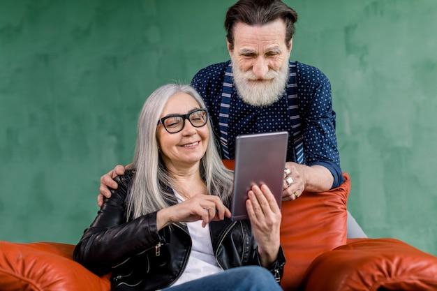 魅力的な年配のカップル、ひげを生やした男、灰色の髪の女性を笑顔の肖像画、デジタルタブレットを使用して一緒に時間を過ごす、インターネットやソーシャルネットワークを閲覧