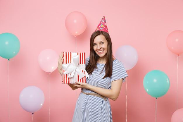 화려한 공기 풍선이 있는 파스텔 핑크색 배경에 선물이 있는 빨간색 상자를 들고 생일 모자 파란색 드레스를 입고 웃는 매력적인 여성의 초상화. 생일 휴가 파티, 사람들은 진심 어린 감정.