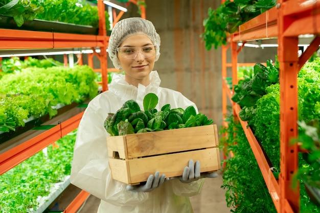 수직 농장에서 식물 상자와 함께 서 있는 안전 고글과 모자에 웃는 매력적인 젊은 농공학자의 초상화