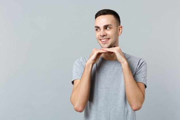 Портрет улыбающегося привлекательного молодого человека в повседневной одежде, смотрящего в сторону, положил руку на подбородок