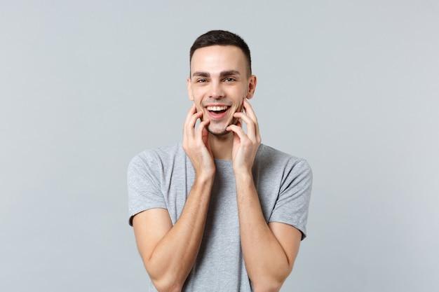 Портрет улыбающегося привлекательного молодого человека в повседневной одежде, положив руки на лицо