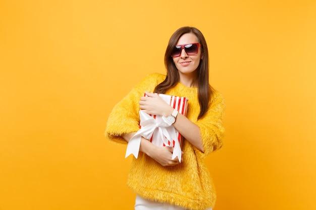 明るい黄色の背景で隔離のプレゼント、ギフトと赤い箱を保持している赤い眼鏡で笑顔の魅力的な若い女性の肖像画。人々の誠実な感情、ライフスタイルのコンセプト。広告エリア。