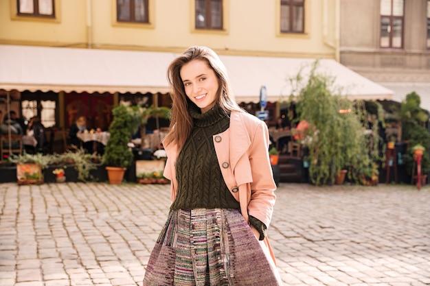 오래 된 도시에 서 있는 웃는 매력적인 젊은 여자의 초상화