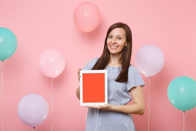 カラフルな気球とパステルピンクの背景に空白の空の画面でタブレットpcコンピューターを保持している青いドレスを着て笑顔の魅力的な若い女性の肖像画。誕生日の休日のパーティーのコンセプト。