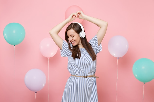 Портрет улыбающейся привлекательной молодой женщины с наушниками в голубом платье, слушая музыку, танцы на пастельно-розовом фоне с красочными воздушными шарами. день рождения, праздник, у людей искренние эмоции.
