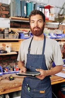 Портрет улыбающегося бородатого плотника в джинсовом фартуке, стоящего в мастерской с планшетным компьютером в руках