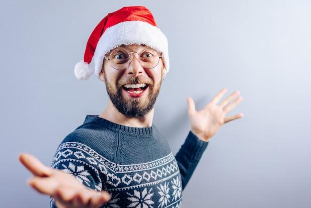 Портрет улыбающегося бородатого парня в шляпе санта-клауса, очках и синем вязаном свитере с пустой серой стеной
