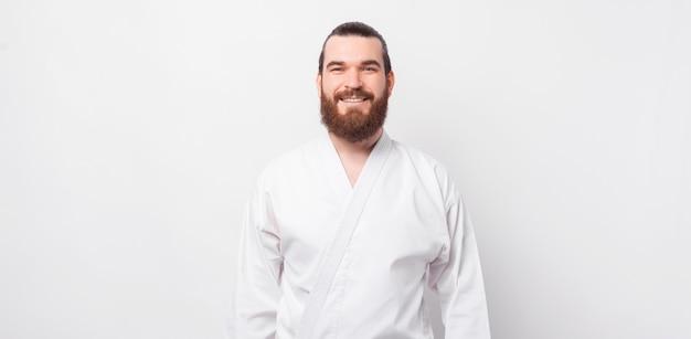 태권도 유니폼을 입고 웃는 수염 된 hipster 남자의 초상화