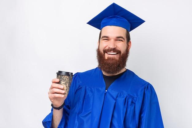 青い独身を着て、コーヒーを持って行く笑顔のひげを生やした学生男の肖像画