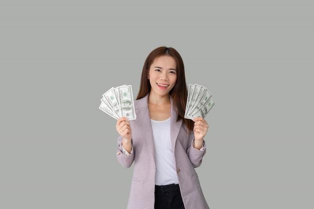たくさんのお金紙幣を保持している笑顔の美しいアジアの女性の肖像画