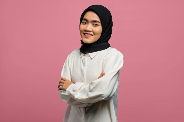 Портрет улыбающейся красивой азиатской женщины в белой рубашке со сложенной рукой