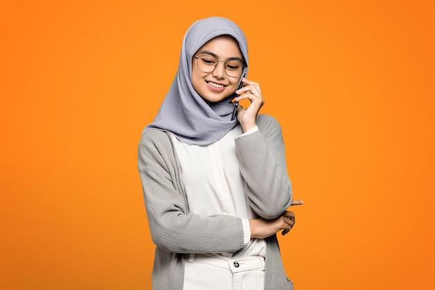 スマートフォンで友人と話している間笑顔の美しいアジアの女性の肖像画