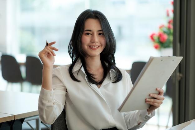コンピューターを使用してオフィスの机で働くスーツと笑顔の美しいビジネスアジアの女性の肖像画
